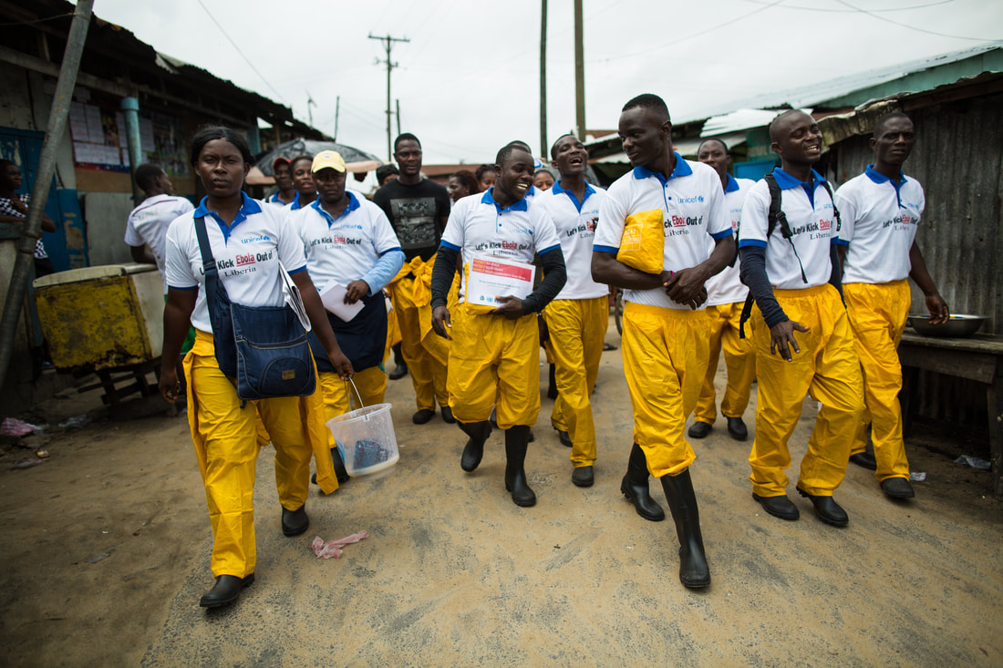 A team of General Community Health Volunteers walk down a street in Liberia. These volunteers were involved in Ebola contact tracing, case finding, awareness, and prevention.