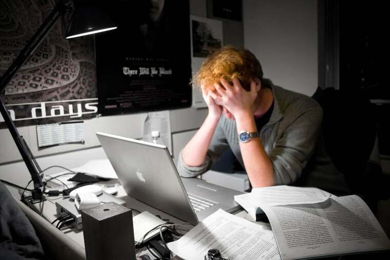 Picture of man frustrated at computer doing work