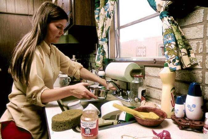 Picture of woman with doing dishes in a messy kitchen