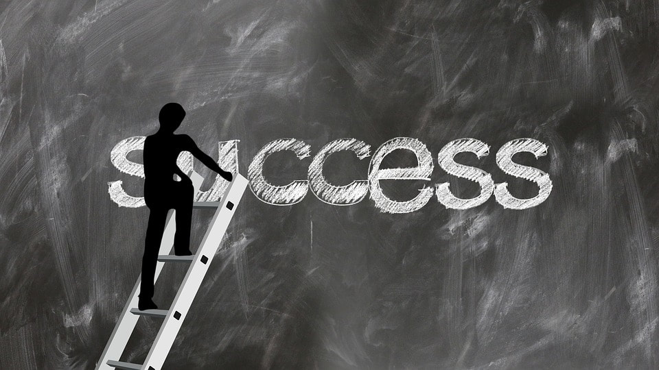 Silhouette of person climbing ladder to the word success.