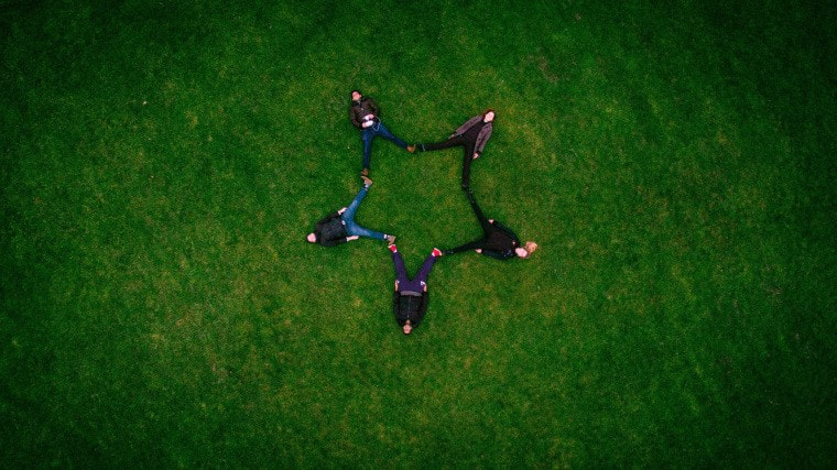 Picture of kids lying on grass field forming a star shape