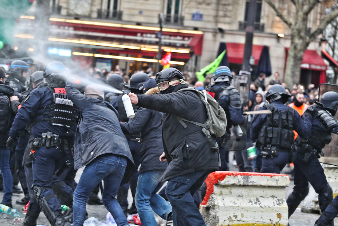 Police with riot sheilds and spray with protestors in Place de la Bastille