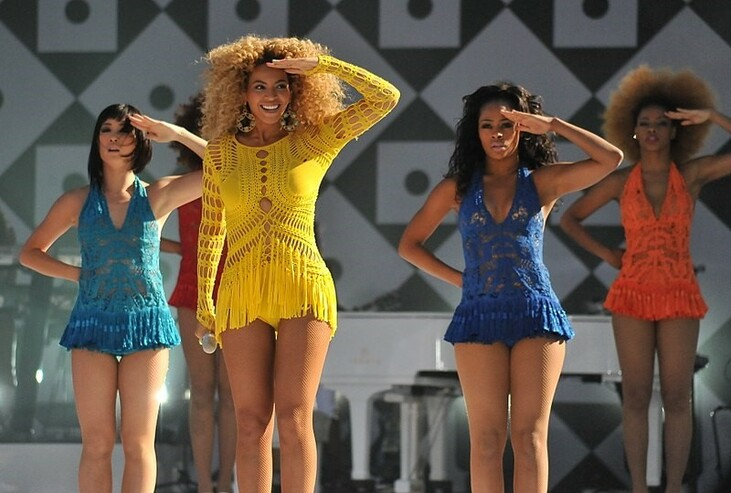 Picture of Beyonce on stage with back up dancers signing Who run the world? Girls.