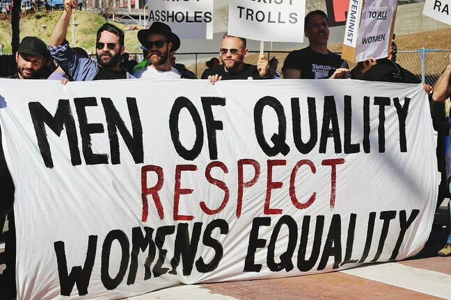 Picture of men holding a sign The sign reads: Men of Quality Respect Womens Equality.