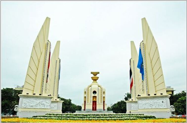 Thailand's democracy monument on a traffic circle in Bangkok, with central feature as cylindrical monument with two golden bowls on top. Four wing like statues stand at four points around the centre representing the four components of the Thai armed forces.