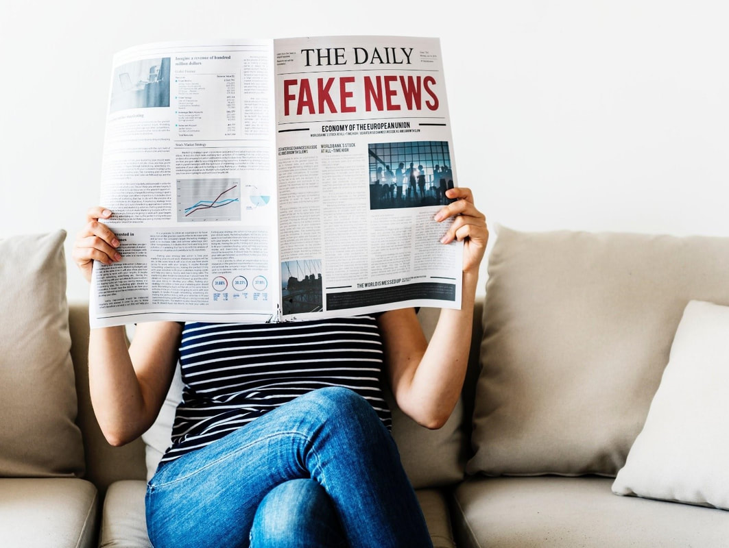 Picture of woman reading The Daily newspaper. Headline reads Fake News.