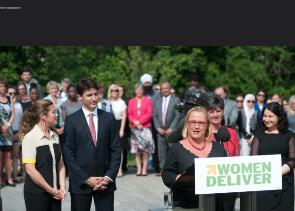 Justin Trudeau stands in support of woman giving speach at podium for Women Deliver event.