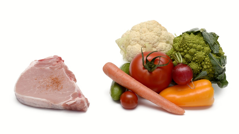 Picture of a piece of meat on one side and a pile of fruit and vegetables on the other.